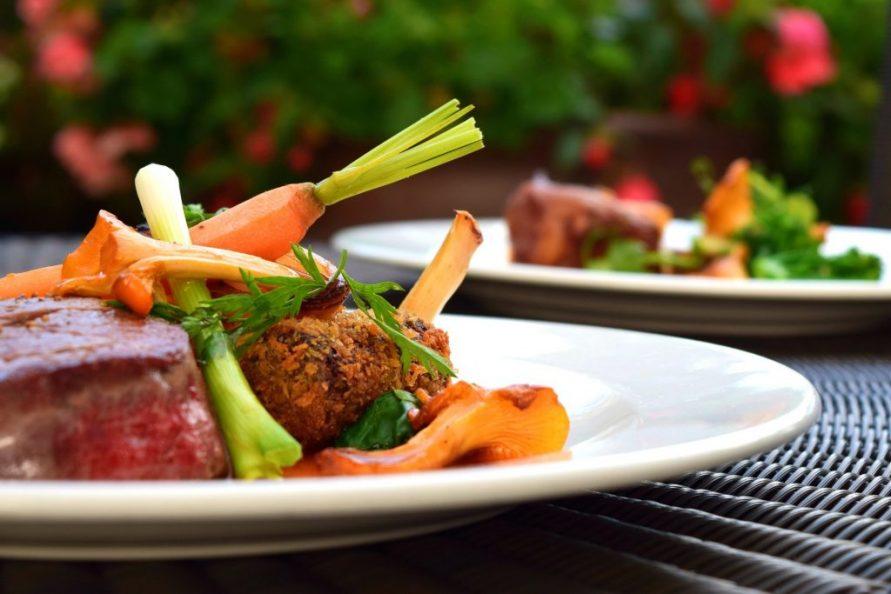 テラスのテーブルに並んだ肉料理