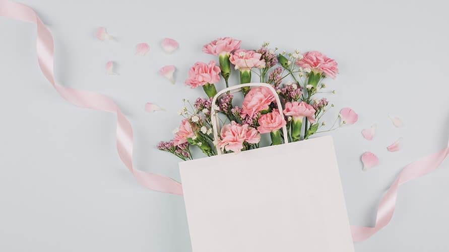白い紙袋に入ったピンク色のカーネーションの花束